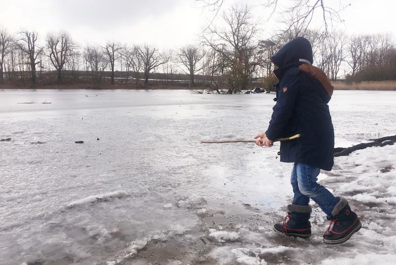 5 jähriger Junge, der am Rande eines fast zugefrorenen Sees steht. Er hat einen Stock in der Hand.